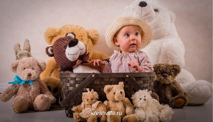 Ребенок в карзине с игрушками. Много плюшевых мишек.