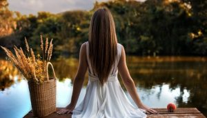 Девушка умиротворенна сидит задом на берегу речки