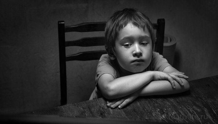 Грустный ребенок сидит один