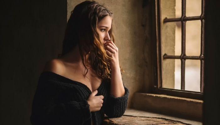 девушка грустная и печальная возле окна