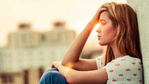 грустная девушка сидит на окне