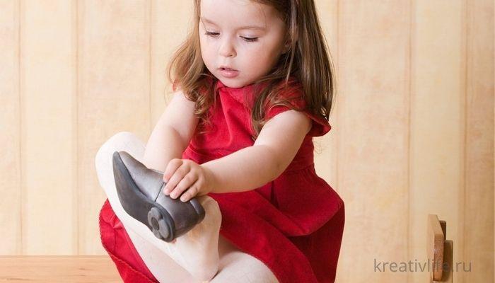 Самостоятельная девочка ребенок одевает обувь