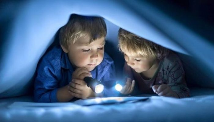 Дети с фонариком читают книгу