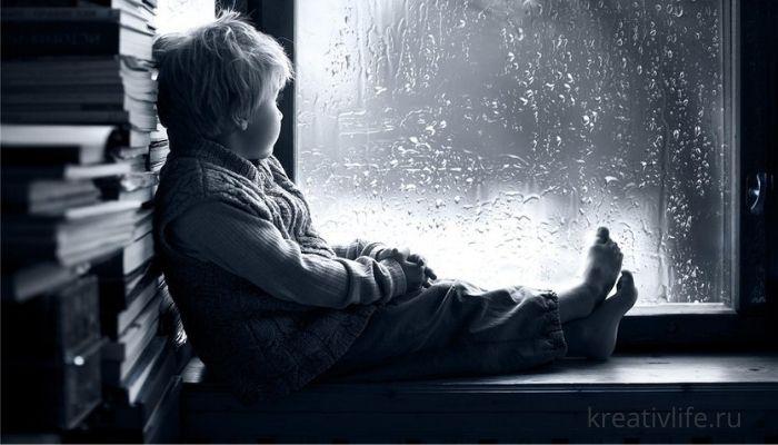 Грустный ребенок сам сидит у окна
