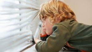 Ребенок дома один смотрит в окно