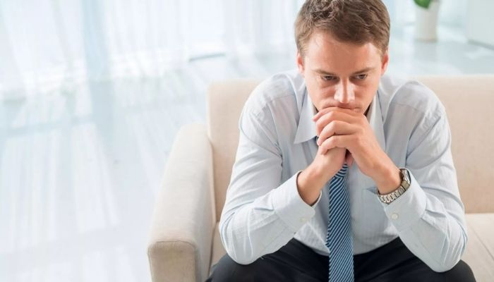 Задумчивый мужчина сидит грустный