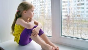 Девочка дома сама сидит на окне