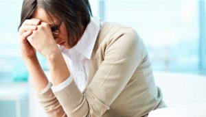Грустная и расстроенная женщина закрыла лицо руками