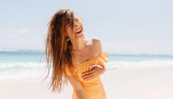 Женщина смеется в купальнике на пляже