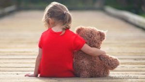 Ребенок девочка сидит с игрушкой