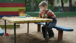 Ребенок один на детской площадке грустный
