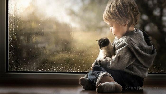 Мальчик ребенок сидит на окне скучает