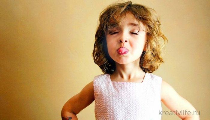 Ребенок кривляется. Красивая девочка показывает язык.