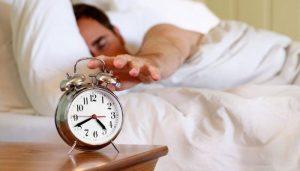 Мужчина спит, звонит будильник