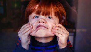 Рыжий мальчик кривляется и корчит гримасы