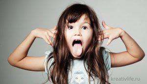 Девочка показывает язык и кривляется