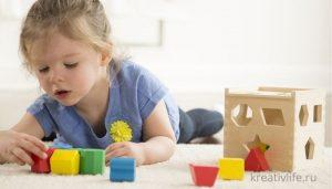 Девочка играет развивающими игрушками из дерева