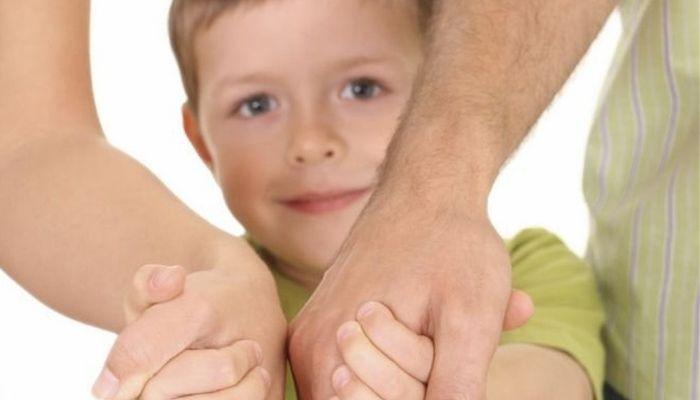 ребенок держит за руку родителей