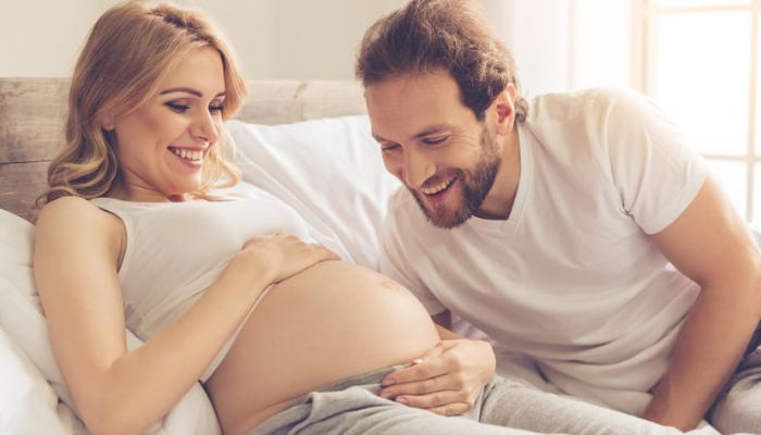 Муж целует живот беременной жене