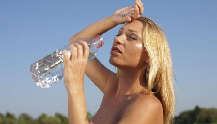 Жара на улице. Девушка пьет воду.