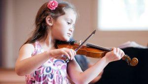 Девочка занимается музыкой играет на скрипке